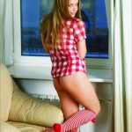 Ankara escort girl Veronica is smiling at the camera, the girl is standing with her back to the camera, she is dressed in a red shirt and red pants, her legs are covered with thick socks to the knee