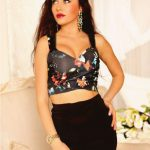 Whatsapp-available girl standing on this picture dressed in long black skirt and flowers-colored top that covers her second-sized breasts