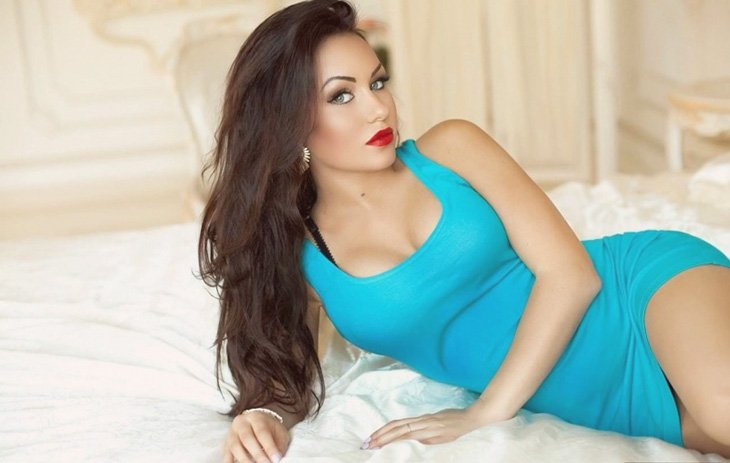 Russian girl is lying on a bed wearing blue dress having a made-up face to the very end of perfection; you'll never get bored with this pussycat