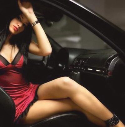 Russian escort Bursa girl looks charmingly in a sexy pose on the couch with a glass of red wine, her long legs are very seductive