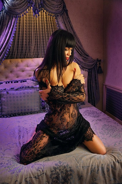 One of the Ankara escort girls Kasya is sitting on a bed showing us her entire body, shyly looking down