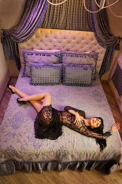 One of the escort girls Ankara Kasya is lying on the bed being covered with a half-transparent black shawl