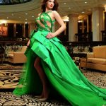 Incall escort agency girl Adelina is in the fascinating green dress in a reception area of a hotel