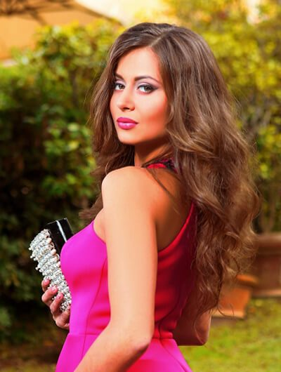 Ankara escorts incall girl is in the dress of saturated pink color with an elegant purse in a hand