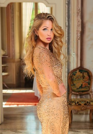Blonde escort Nicole is standing in a flamboyant interior in very fancy evening dress