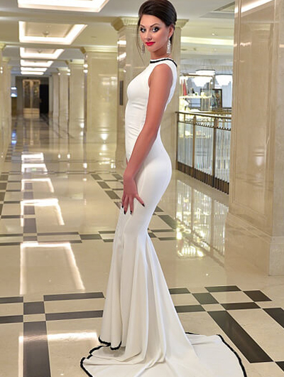 Ankara escort bayan Sabina stands in a hall of a marbled passage wearing a sexy tight white dress