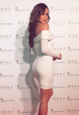 Outcall escorts girl Slava in a white dress is on a red carpet of an entrance to a fashion show