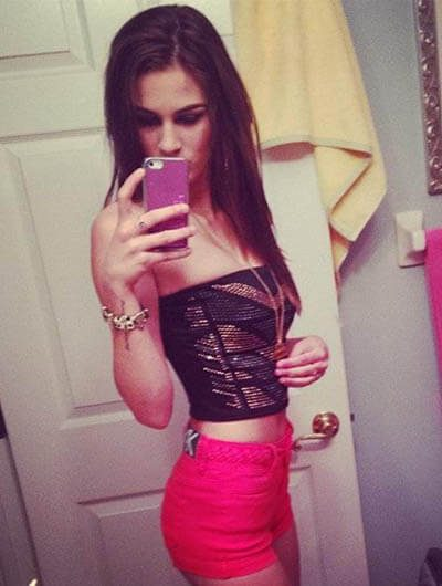Ankara escort outcall Roxana is taking a shot of her in a mirror, wearing top and shorts