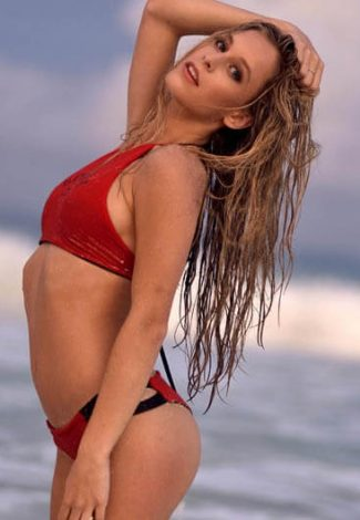 Blonde escorts girl stands near the water grabbing her wet hair holding them back
