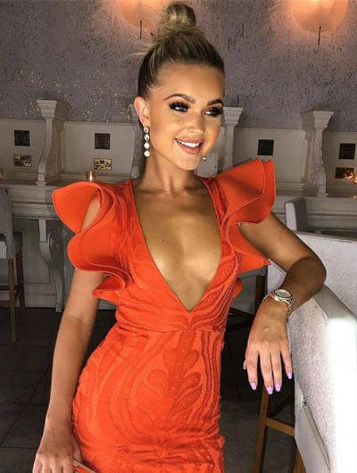 Ankara escort bayan in an expensive red dress stands in a marbled hall having evening makeup