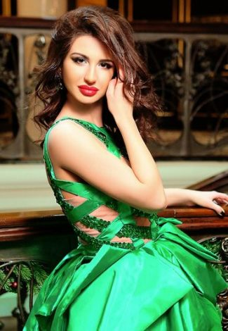Incall escort agency girl Adelina in green fancy evening dress is in the hall of a Turkish hotel