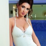 Incall escort agency girl Adelina is in the white swimsuit in the pool area of a hotel