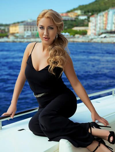Escort Ankara incall girl is sitting on a verge of a yacht trying to seduce you with an elegant look