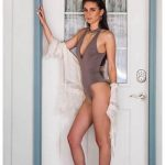 Ankara escort outcall Roxana in the swimsuit is standing in the door, wearing a light shawl