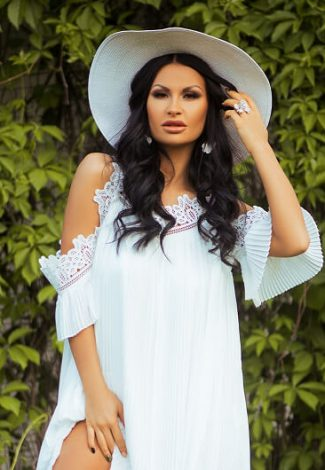 Ankara escort katalog girl Alexandra in the white apparel and a hat is in the green garden