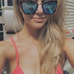 Russia escort agency girl Tanya takes a selfie sitting in a chaise lounge having a suntan