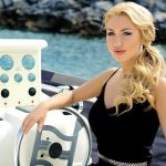 Escort Ankara incall girl Aurora smiles playing the role of a captain of a boat