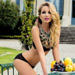 Blonde escort Nicole is in the garden with a pod of fruits, wearing only black underwear