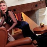 Bayan eskortlar Caroline is in the stylish dark-blue dress sits in a leather chair